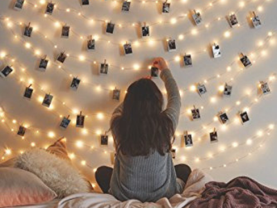girl hanging photos on a string of lights