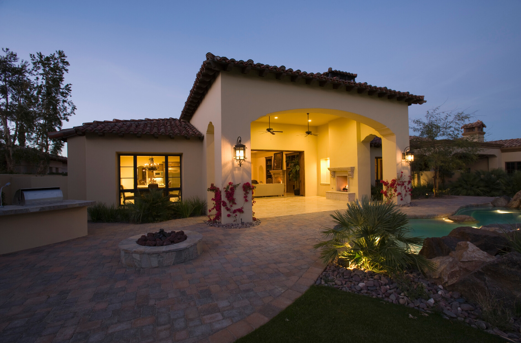 home exterior at dusk with landscape lighting, brick paver pathway and a firepit