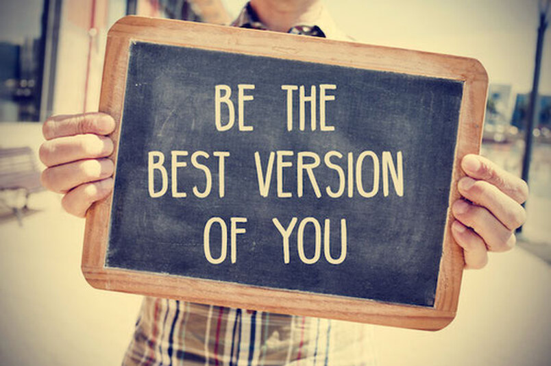 man holding a chalk board that says be the best version of you